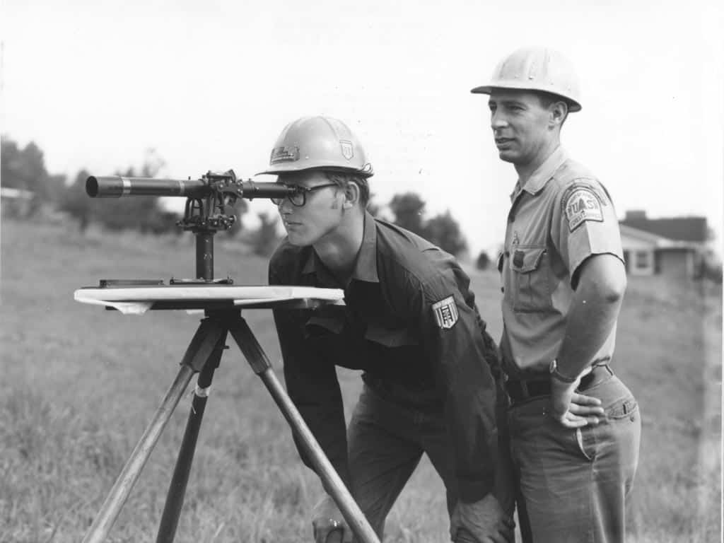 Corpsmen working under the supervision of a crew foreman learn to do plane table mapping on the job. Flatwoods Job Corps, Jefferson National Forest, Virginia, c. 1968.