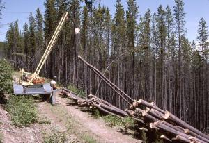 Employees use a Bitterroot Mini Yarder, a low cost and mobile cable yarding system. The Bitterroot Mini Yarder is trailer mounted and pulled behind a pickup truck. (USDA)